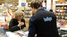 A customer pays at the cash of an Indigo Books store in Toronto in this April 8, 2011, file photo. (Fernando Morales/The Globe and Mail)