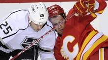 Los Angeles Kings' Dustin Penner, left, collides with Calgary Flames' Cory Sarich during second period NHL action, in Calgary, Alta., Saturday, Jan. 14, 2012. THE CANADIAN PRESS/Larry MacDougal (Larry MacDougal)