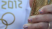 A torchbearer holds onto her torch in England May 19, 2012. (Toby Melville/Reuters/Toby Melville/Reuters)