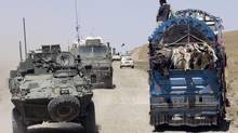A convoy of Canadian military vehicles drives by a truck loaded with cattle as they move into the forward operating base in Spin Boldak, Afghanistan, on May 5, 2007. (RYAN REMIORZ/THE CANADIAN PRESS)