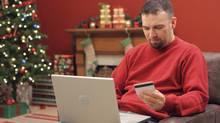 Man shopping for Christmas gifts online (Daniel Hurst/Photos.com)