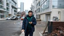 Adam Ferraro, a Toronto-based strategic planner in advertising, checks his phone on his walk to work. (Galit Rodan/The Globe and Mail)