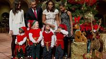 The first family, from left, Malia Obama, President Barack Obama, first lady Michelle Obama, and Sasha Obama, join children dressed like elves at the National Building Museum in Washington, Sunday, Dec. 15, 2013. (MANUEL BALCE CENETA/AP)