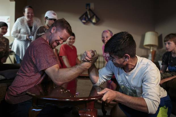 Ziad Hamam, 14, battles Mark Loewen in an arm wrestle during brother Hussein's first birthday party. Mark and his wife, Amy, are two of the Hamams' key sponsors.