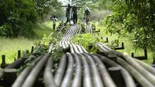 Local youths walk on Shell Oil pipeline in Utorogun, Nigeria, in a file photo. (GEORGE OSODI/AP)