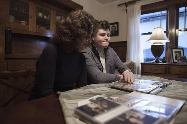 Lola Doyle and her son Jackson look over photographs of Lola's father Barry Hyman at their home in Vancouver.