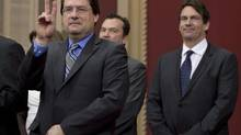 Opposition MLA Bernard Drainville gestures to applauds as PQ members are sworn in, Tuesday, April 22, 2014 at the legislature in Quebec City. MLA Pierre Karl Peladeau, right, looks on. (Jacques Boissinot/THE CANADIAN PRESS)