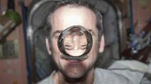 Canadian Space Agency astronaut Chris Hadfield watches a water bubble float between him and the camera. (NASA/Reuters)