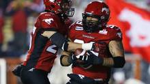 Calgary Stampeders' Corey Mace, right, celebrates his touchdown with teammate Rob Cote during the first half of their CFL football game against the BC Lions in Calgary, Alberta, October 26, 2012. (Reuters)