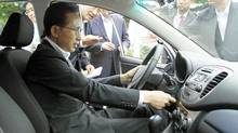 South Korean President Lee Myung-Bak dirves Hyundai's first full-speed electric vehicle, BlueOn, during an unveiling ceremony at the presidential Blue House in Seoul on Sept. 9, 2010. (DONG-A ILBO/AFP/Getty Images)