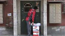 Chen Honglei, a 26-year-old courier with Jingdong, also known as JD.com, China's second largest e-commerce company rings the bell of an apartment where he is making a delivery, in Beijing, November 20, 2013. The rise of e-commerce is giving economic refuge to the poor and nonconformists in China. (STAFF/REUTERS)