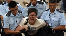 A demonstrator is taken away by police after hundreds of protesters staged peaceful sit-ins overnight on a street in the financial district in Hong Kong on July 2, 2014, following a huge rally to show their support for democratic reform and oppose Beijing's desire to have the final say on candidates for the chief executive's job. (VINCENT YU/ASSOCIATED PRESS)