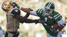Saskatchewan Roughriders running back Kory Sheets runs the ball past Winnipeg Blue Bombers defensive back Brandon Stewart during the second half of CFL football action in Regina, Sask., Sunday, September 02, 2012. (The Canadian Press)