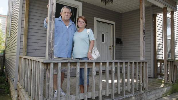 Joseph Keller and his wife Jennifer stand on the porch of their abandoned house in Columbus, Ohio on Sept. 30, 2012. The Kellers are among thousands of U.S. homeowners legally liable for houses they didn't know they still owned, after banks decided not to complete foreclosures. (JAY LAPRETE/REUTERS)