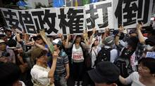 Protesters raise placards during a rally against Japan's Prime Minister Shinzo Abe's push to expand Japan's military role, in front of Abe's official residence in Tokyo July 1. (ISSEI KATO/REUTERS)