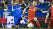 Montreal Impact's Lamar Neagle, left, and Toronto FC's Richard Eckersley battle for the ball during second half in Montreal, Saturday, April 7, 2012. (Graham Hughes/Graham Hughes/THE CANADIAN PRESS)