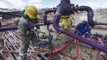 In this March 29, 2013 file photo, workers tend to a well head during a hydraulic fracturing operation at an Encana gas well. (Brennan Linsley/THE ASSOCIATED PRESS)