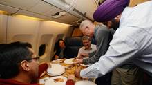 Prime Minister Stephen Harper shares a plate of samosas with reporters and colleges on the Canadian air bus in his private quarters while on route to India from Ottawa on Saturday, November 3, 2012. While in Asia Harper will also visit the Philippines and Hong Kong. (Sean Kilpatrick/THE CANADIAN PRESS)