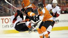Philadelphia Flyers' Harry Zolnierczyk, center, collides with Ottawa Sentors' Mike Lundin, left (Michael Perez/AP)