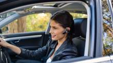 Woman in car with cell phone earphone (Jupiterimages/Getty Images/Comstock Images)