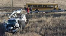 Officials investigate at the scene of a school bus crash near Crossfield, north of Calgary, Alta., on Oct. 25, 2013. Crossfield's Mayor says the conditions of the children – three of whom were critically injured, and six of whom were seriously injured – are improving. (Larry MacDougal/The Canadian Press)
