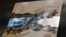 A hologram security feature is seen on the new Canadian 100 dollar bill made of polymer in Toronto November 14, 2011. The Bank of Canada purged the image of an Asian-looking woman from its new $100 banknotes after focus groups raised questions about her ethnicity. (MARK BLINCH/REUTERS)