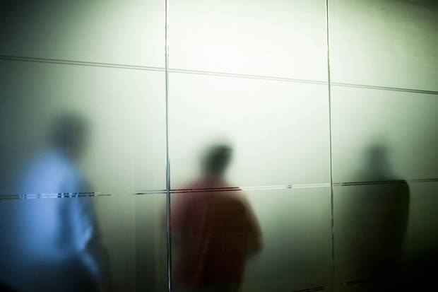 Vision Critical employees are seen through a glass wall during a 2013 meeting.