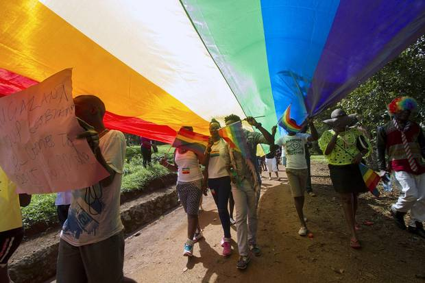 People walk under a giant rainbow flag as they take part in the Gay Pride parade in Entebbe on August 8, 2015. Homosexuality remains illegal in Uganda, punishable by a jail sentence.