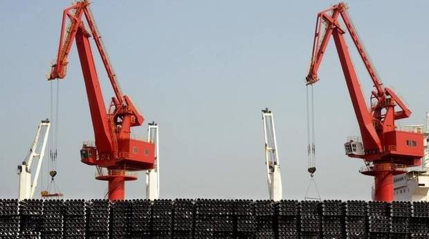 Piles of steel pipes to be exported are seen in front of cranes at a port in Lianyungang, Jiangsu province March 7, 2015.