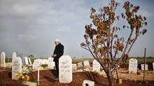Abdlhamid Haj Omar, 70, a father who lost three sons and two grandsons in the ongoing Syrian crisis, prays as he visits their graves at the Martyrs' cemetery in Azaz city, North Aleppo, December 25, 2012. (AHMED JADALLAH/REUTERS)