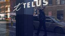 A pedestrian is reflected in the window of a Telus store while using a mobile phone in Ottawa. (CHRIS WATTIE/REUTERS)