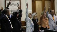 Sen. Wendy Davis, D-Fort Worth, centre, who tried to filibuster an abortion bill, holds up a no vote as time runs out on an abortion bill vote, Wednesday, June 26, 2013, in Austin, Texas. (Eric Gay/AP)