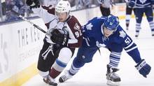 Toronto Maple Leafs defenceman Jake Gardiner, right, takes out Colorado Avalanche forward Gabriel Landeskog, left, during first period NHL hockey action in Toronto on Tuesday, Oct. 8, 2013. (Nathan Denette/THE CANADIAN PRESS)