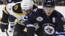 Boston Bruins' Milan Lucic (17) and Winnipeg Jets' Tobias Enstrom (39) battle for the puck during first period NHL hockey action in Winnipeg, Friday, February 17, 2012. THE CANADIAN PRESS/Trevor Hagan (Trevor Hagan/CP)