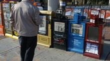 Pedestrians pass newspaper boxes in Toronto. New figures suggest that, while fewer people are reading traditional newspapers, they are still turning to established publications when looking for their news online. (Louie Palu/The Globe and Mail)