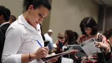 A woman fills out a job application during the Gemological Institute Of America (GIA)'s Jewelry Career Fair in New York in this file photo taken July 30, 2012. (Shannon Stapleton/Reuters)