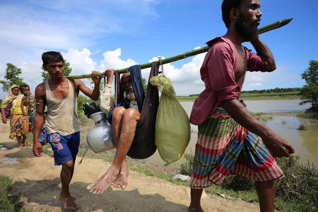 """Abdur Sabur and Mohammad Enayatullah carry their elderly uncle into Bangladesh, after picking him up in Myanmar, where Mr. Sabur said he saw """"rivers of blood."""" Soldiers in Myanmar also opened fire on them. Deadly violence against Rohingya Muslims has escalated in Myanmar's Rakhine State."""