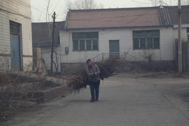 A villager hauls wood through smog-filled air to burn for cooking in Songting village.