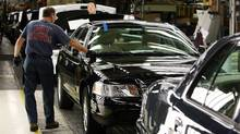 Factory employees work on Ford Crown Victoria vehicles on Thursday, September 8, 2011 at the Ford Assembly Plant in St. Thomas, Ont. The Canadian Auto Workers and the three big North American automakers are continuing contract talks in the shadow of a possible strike, but there's word of some progress. (Dave Chidley/The Canadian Press)