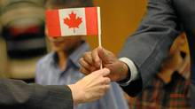 New Canadian citizens receive Canadian flags after a citizenship ceremony at the Toronto's CIC office at St. Clair Ave. (Fernando Morales/The Globe and Mail/Fernando Morales/The Globe and Mail)