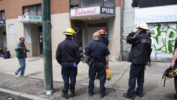 Vancouver firefighters gather outside the Balmoral Hotel.