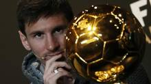 FIFA Men's Ballon d'Or of the Year 2012 nominee Lionel Messi of Argentina watches the trophy during a news conference before the FIFA Ballon d'Or 2012 soccer awards ceremony at the Kongresshaus in Zurich January 7, 2013. (MICHAEL BUHOLZER/REUTERS)