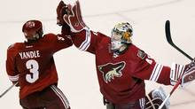 Phoenix Coyotes goalie Mike Smith, right, celebrates their 5-3 win over the Nashville Predators with Keith Yandle (3) after Game 2 in an NHL hockey Stanley Cup Western Conference semi-final playoff series. (Ross D. Franklin/Associated Press)