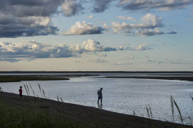 A man wades into the water while walking along Kelly Beachin Kouchibouguac National Park.
