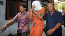 Indonesian police officers escort Tommy Schaefer, middle, to a hospital for medical check on Aug. 15, 2014. (FIRDIA LISNAWATI/ASSOCIATED PRESS)