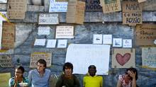 Portuguese and Spanish youths sit in front of myriad banners as they camp on May 23, 2011 at Rossio Square in Lisbon as they protest against the economic crises and high unemployment