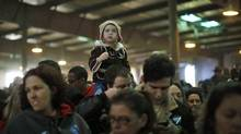 A girl sits on her father's shoulders as they await the arrival of U.S. President Barack Obama at a campaign rally in Hilliard, Ohio, November 2, 2012. (Jason Reed/REUTERS)