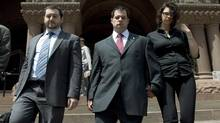 Constable James Forcillo, centre, flanked by his wife Irina Forcillo and lawyer Lawrence Gridin, leave court Tuesday. (Nathan Denette/CP)