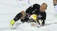 United States goalkeeper Brad Guzan slides in the snow to make a save against Costa Rica (JACK DEMPSEY/The Associated Press)