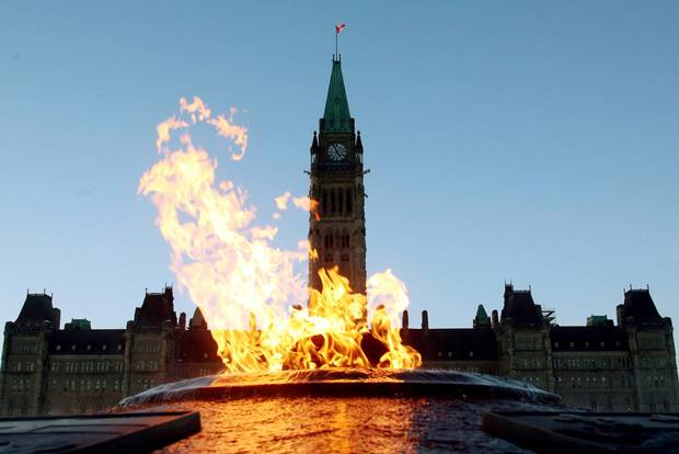 The Centre Block of the Parliament Buildings is shown through the Centennial Flame on Parliament Hill in Ottawa on Sunday, January 25, 2015.